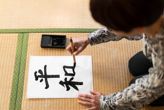 Nahaufnahme frau, die japanischen brief malt