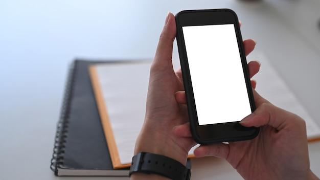 Nahaufnahme frau hände halten smartphone mit weißem bildschirm.