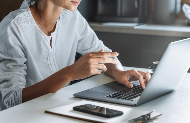 Nahaufnahme frau hände mit einem laptop während der arbeit oder studieren von zu hause aus. bildung oder online arbeiten. fernarbeitskonzert