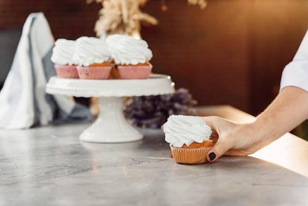 Nahaufnahme frau hand hält einen frischen leckeren cupcake mit einer weißen creme und legt es auf ein weißes tablett.
