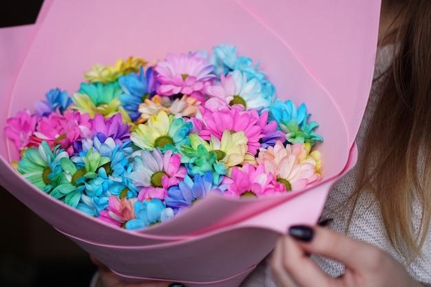 Nahaufnahme - frau mit buntem regenbogenstrauß in rosa verpackung