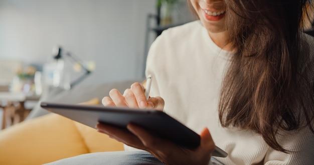 Nahaufnahme freiberufliche asiatische dame freizeitkleidung mit tablet online lernen im wohnzimmer zu hause. arbeiten sie von zu hause aus, arbeiten sie aus der ferne.