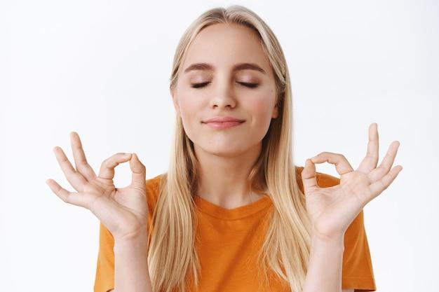 Nahaufnahme friedliches, entschlossenes und gesundes, gut aussehendes blondes mädchen in orangefarbenem t-shirt, enge augen, die zen-gesten machen, meditieren, enge augen meditieren und erleichtert lächeln, yoga-atemübungen machen