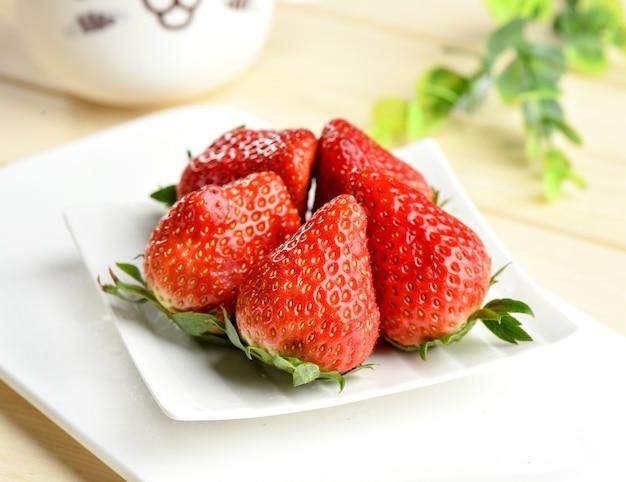 Nahaufnahme frische erdbeere und blätter auf holztisch