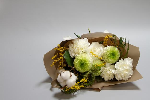 Nahaufnahme frühlingsstrauß von mimosenzweig, chrysantheme, ranunkel, baumwolle, nelke, selektiver fokus