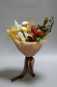 Nahaufnahme frühlingsstrauß von ruscus, leukadendron, leukospermum, iris, baumwolle, mimosenzweig, tulpe, selektiver fokus