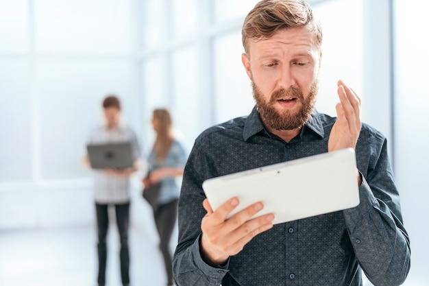 Nahaufnahme. frustrierter mann, der auf den bildschirm seines tablets schaut