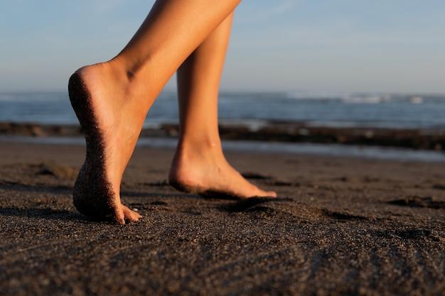Nahaufnahme. füße auf schwarzem sand. bali