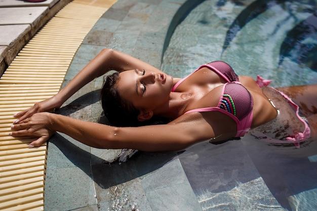 Nahaufnahme gebräunte teile des weiblichen körpers, die nahe mit pool sexy modell liegen
