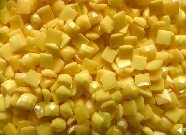 Nahaufnahme, gelbe quadratische diamanten für die diamantstickerei. hobbys und heimwerken, materialien zum erstellen von diamantstickereien.