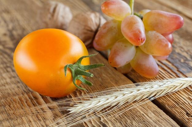 Nahaufnahme gelbe tomate mit trauben, walnüssen und weizenähre auf alten holzbrettern. geringe schärfentiefe. herbstszene.