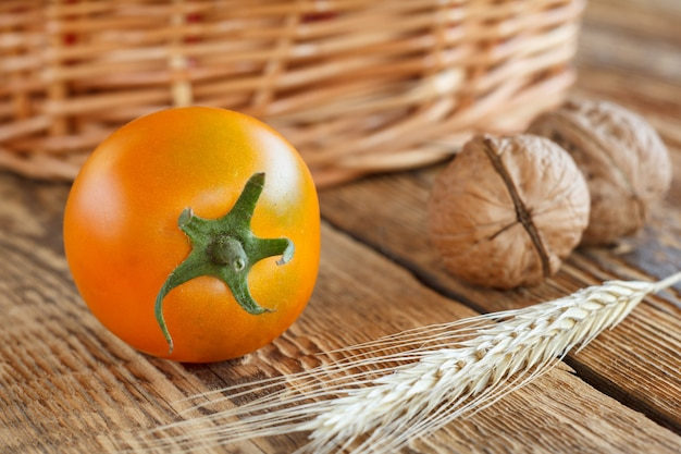 Nahaufnahme gelbe tomate, walnüsse, weizenähren und weidenkorb auf holzhintergrund. geringe schärfentiefe.