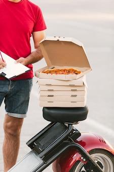 Nahaufnahme geöffneter pizzakasten auf motorrad