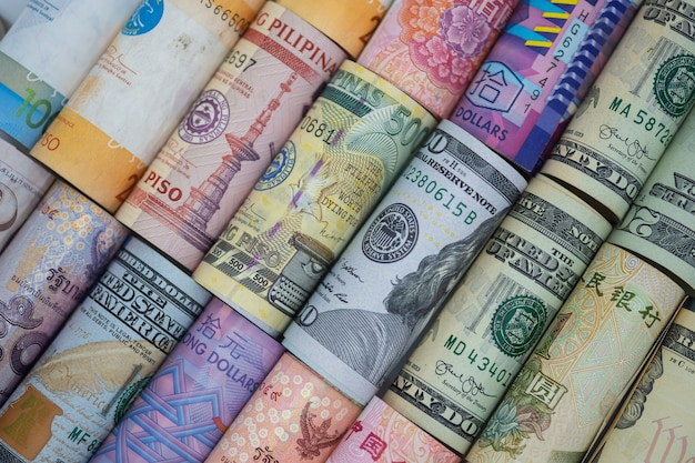 Nahaufnahme gerollt von der vielzahlbanknote auf der ganzen welt. wechselkurs und forex-anlagekonzept