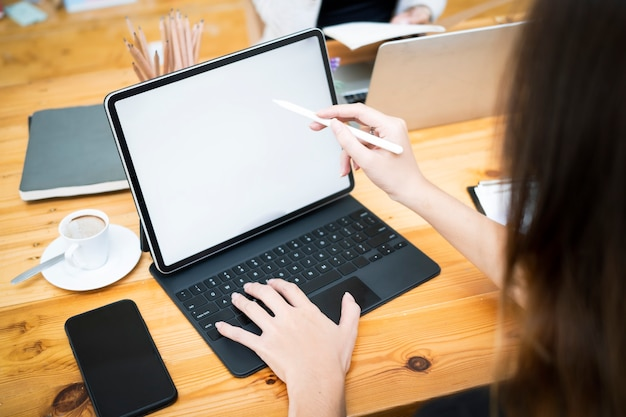 Nahaufnahme geschäftsfrau, die stylus-stift hält und auf dem bildschirm des digitalen tablets zeigt.