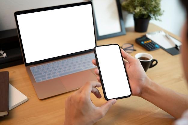 Nahaufnahme geschäftsmann am schreibtisch sitzen und smartphone verwenden. Premium Fotos