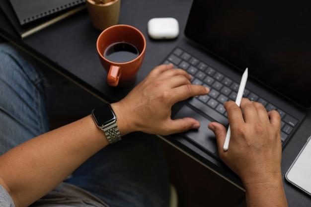Nahaufnahme, geschäftsmann, der auf tragbarem tablet tippt, männlicher händler analysiert daten im modernen co-working-space