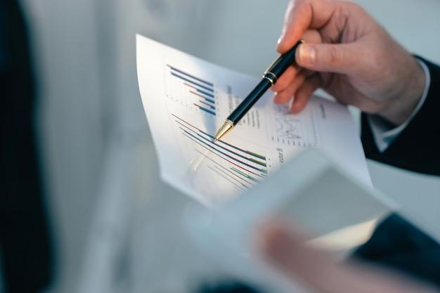 Nahaufnahme. geschäftsmann, der finanzdiagramm analysiert. business-hintergrund