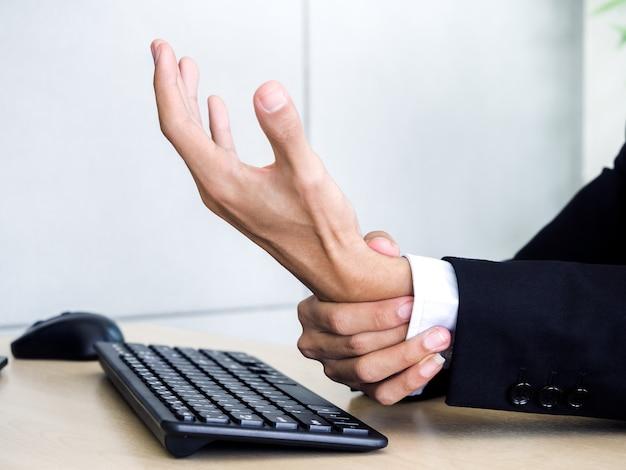 Nahaufnahme-geschäftsmann im anzug, der handschmerz erhält, während notebook-computer im büro verwendet wird