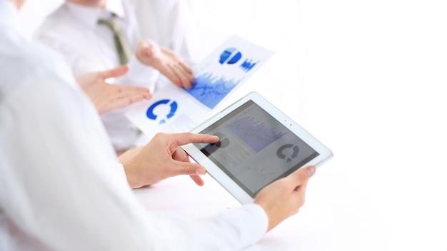 Nahaufnahme. geschäftsmann mit einem digitalen tablet, das ein finanzielles chart.photo mit einer kopie des raumes analysiert.