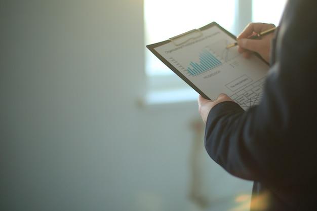 Nahaufnahme. geschäftsmann studiert ein finanzdokument. foto mit kopienraum