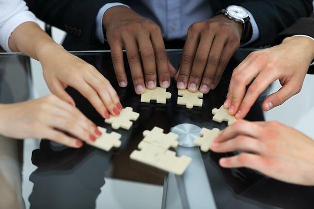 Nahaufnahme.geschäftspartner, die für die puzzleteile verantwortlich sind. konzept der zusammenarbeit