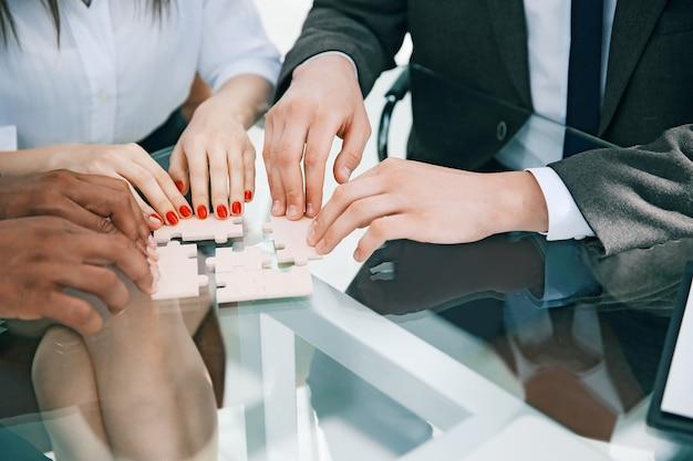 Nahaufnahme. geschäftsteam, das puzzle zusammenbaut, das hinter einem schreibtisch sitzt. das konzept der strategie im geschäft