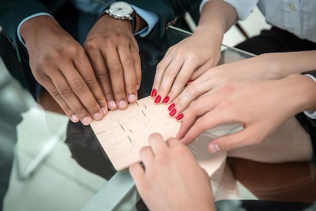 Nahaufnahme. geschäftsteam, das puzzle zusammensetzt, das hinter einem schreibtisch sitzt. das konzept der strategie im geschäft