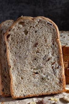 Nahaufnahme geschnittenes kornvollkornbrot auf dunklem rustikalem hölzernem hintergrund, biozutaten, gesundes essen.