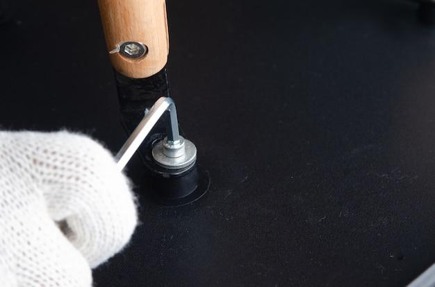 Nahaufnahme geschossen, hand des schraubenden weges des tischlers der stühle mit hexeschlüssel