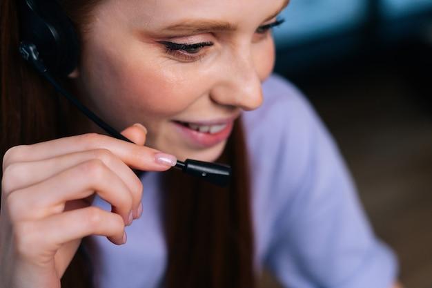 Nahaufnahme gesicht der lächelnden jungen frau operator mit headset während der kundenbetreuung zu hause.