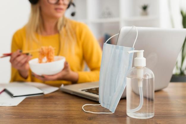Nahaufnahme gesichtsmaske und händedesinfektionsmittel auf dem schreibtisch