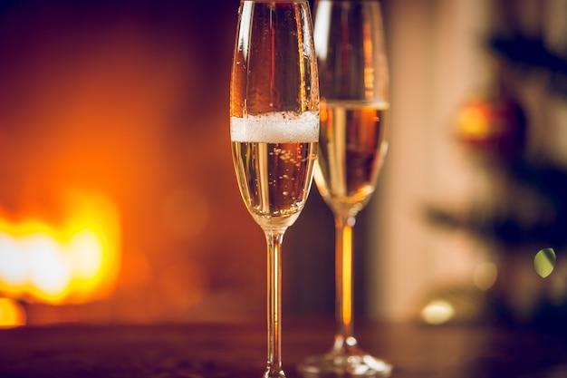 Nahaufnahme getöntes bild von zwei gläsern champagner neben dem kamin
