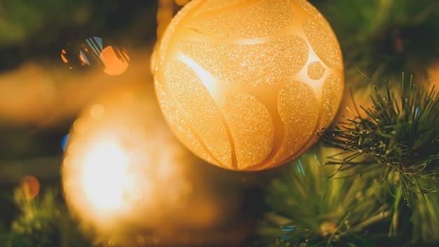 Nahaufnahme getöntes bild von zwei goldenen kugeln mit glitzern, die am weihnachtsbaum hängen