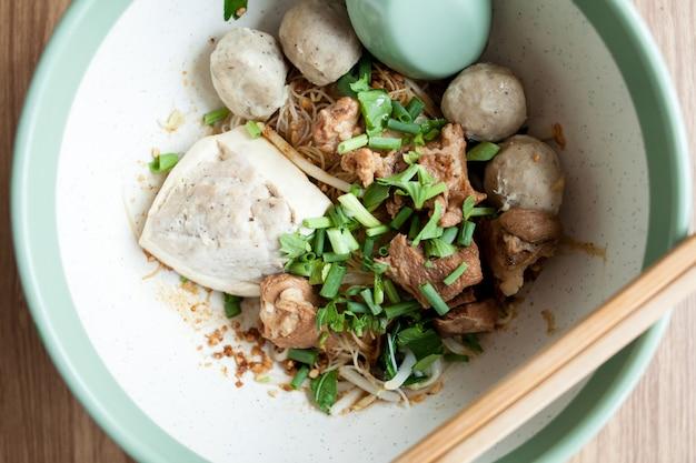 Nahaufnahme getrocknete nudeln mit tofu-schweinefleisch, fleischbällchen und gekochtem schweinefleisch in der großen schüssel auf holz hintergrund