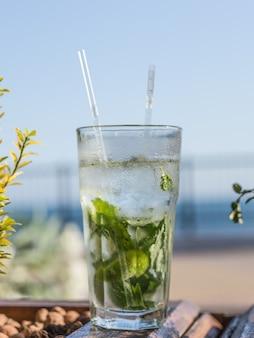 Nahaufnahme glas des alkoholfreien mojito-cocktails mit limette und minze verziert mit limettenscheibe und mit zwei röhren am barhintergrund.