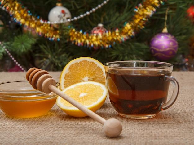Nahaufnahme glastasse tee, zitronen- und honigstücke in glasschüssel mit holzlöffel auf dem tisch mit sackleinen und weihnachtsbaum mit spielzeugbällen und girlanden im hintergrund.