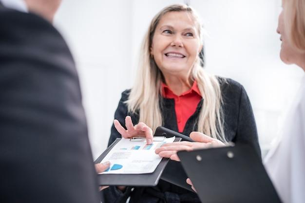 Nahaufnahme. glückliche geschäftsfrau, die finanzbericht betrachtet. geschäftskonzept