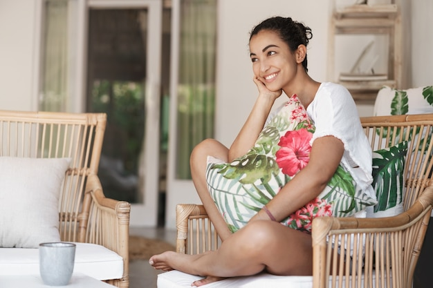 Nahaufnahme glückliche gesunde junge frau mit dunklem lockigem haar, das im bequemen sofa in einer terrasse sitzt