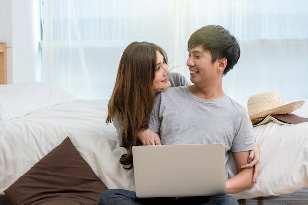 Nahaufnahme-glücklicher asiatischer liebhaber oder paare, die bei der anwendung des technologielaptops auf dem bett in b sprechen und lächeln