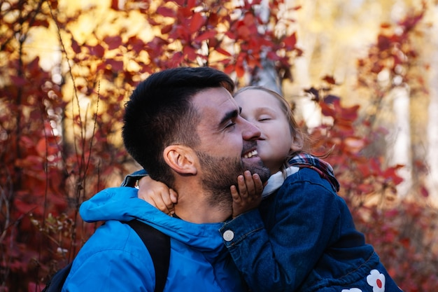 Nahaufnahme glücklicher vater porträt nettes kleines mädchen küsst glücklich lächelnden vater mit dunklen haaren im herbst f...
