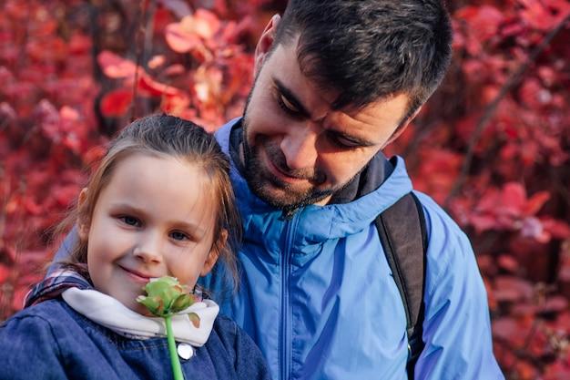 Nahaufnahme glückliches familienkonzept glücklicher mann in blauer jacke blick auf hübsches mädchen mit blume im herbst ...