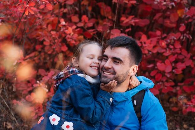 Nahaufnahme glückliches familienporträt glücklich lächelnder vater mann mit dunklen haaren hält seine lächelnde kleine tochter...