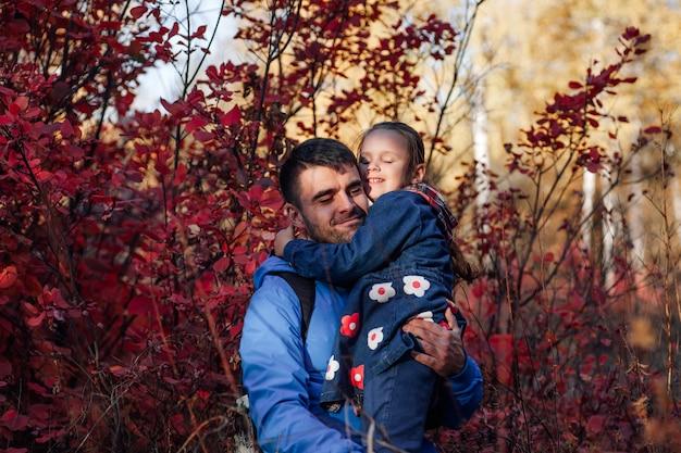 Nahaufnahme glückliches familienporträt glücklicher vater hält lächelnde kleine tochter in blauer jacke im herbst für...