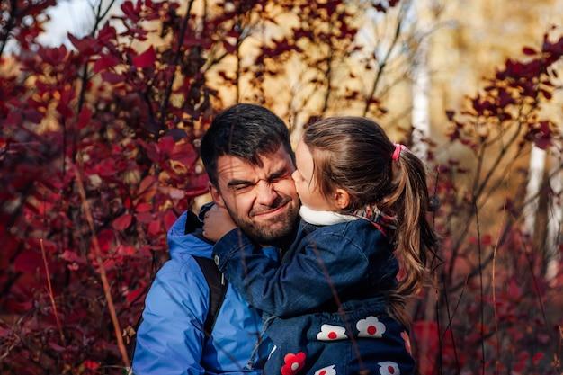 Nahaufnahme glückliches familienporträt süßes kleines mädchen halten und küssen ihren vater in blauer jacke im herbst für ...
