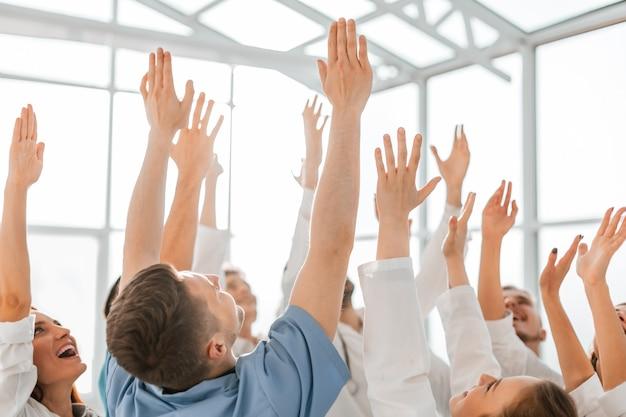 Nahaufnahme. glückliches team von medizinern mit den händen hoch. erfolgskonzept