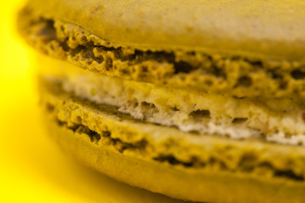Nahaufnahme großer makronen-kokos-geschmack auf gelbem hintergrund.