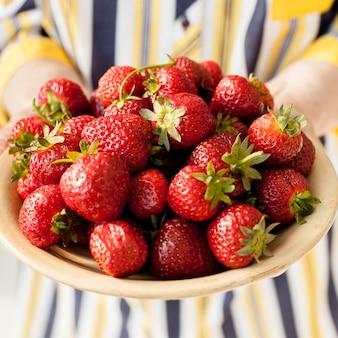Nahaufnahme großmutter, die erdbeeren hält
