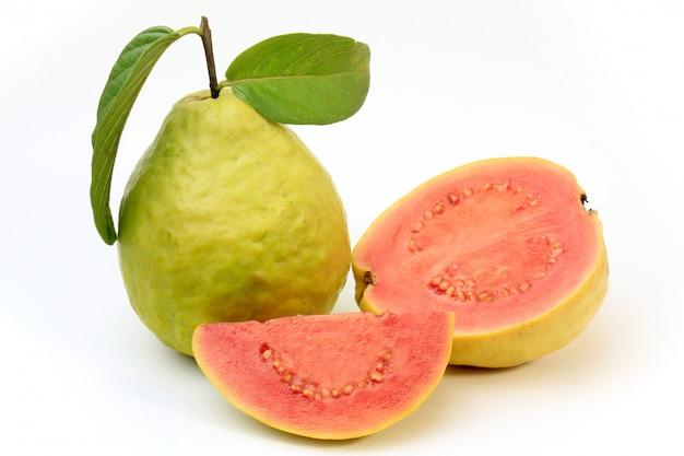 Nahaufnahme guajava-frucht, rosa, frisch, organisch, mit den blättern, ganz und geschnitten, lokalisiert auf weißem hintergrund. vorderansicht