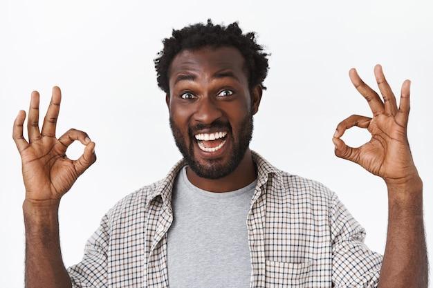 Nahaufnahme gutaussehender aufgeregter, amüsierter bärtiger afroamerikaner, genehmigen sie etwas gutes